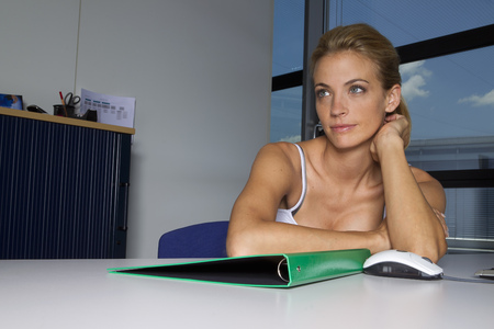 accomplishes: Woman sitting with folder at desk LANG_EVOIMAGES