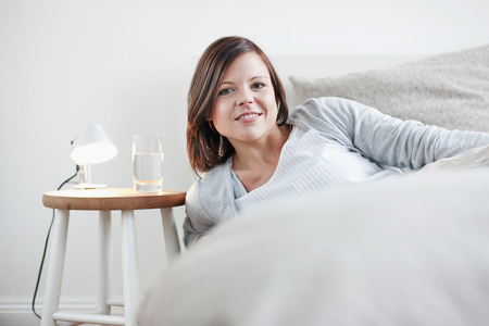 gratified: Woman sitting up in bed