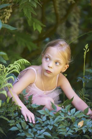 Girl in ballet costume hiding in bush