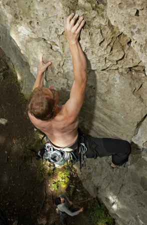 remoteness: Man climbing rock face in forest