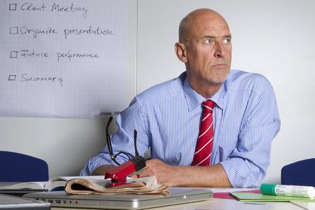 Businessman sitting at desk in office LANG_EVOIMAGES