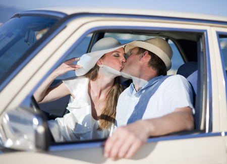 honeymooner: Newlywed couple kissing in car