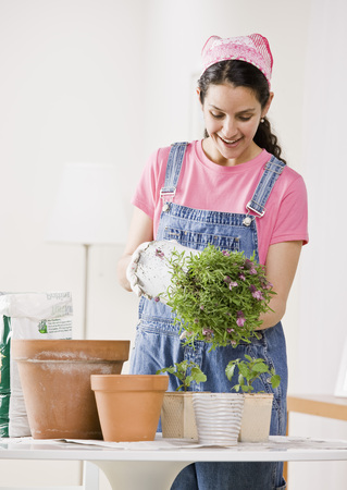 Woman depotting plants at home LANG_EVOIMAGES