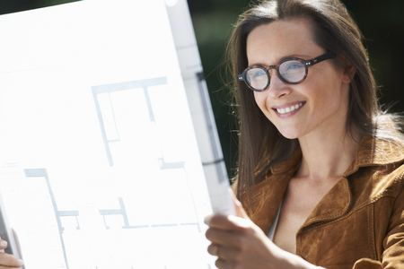 gratified: Woman reading blueprints outdoors LANG_EVOIMAGES