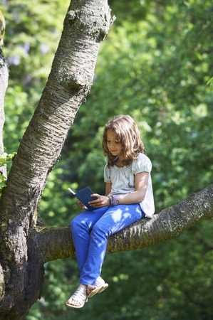 Girl reading in tree outdoors LANG_EVOIMAGES