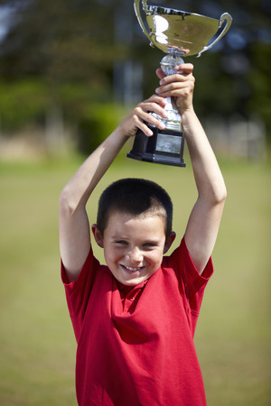 Boy cheering with trophy outdoors LANG_EVOIMAGES
