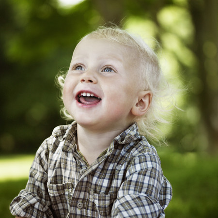 gratified: Close up of boy laughing outdoors LANG_EVOIMAGES