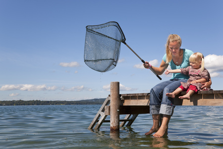 Mother and daughter fishing with net LANG_EVOIMAGES