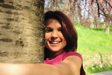 environmental issues: Smiling woman hugging tree