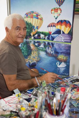 Older artist painting in studio