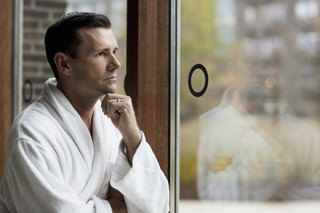 Man in bathrobe looking out window