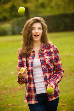 tosses: Teenage girl juggling apples in park