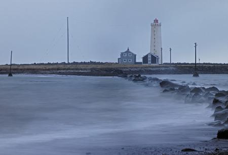 stormy waters: Waves crashing on rocks near lighthouse