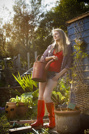 Woman holding watering can in garden LANG_EVOIMAGES