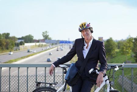 Businessman with bicycle on bridge