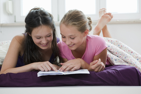 gratified: Girls reading together on bed
