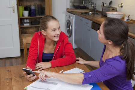 gratified: Mother helping daughter with homework