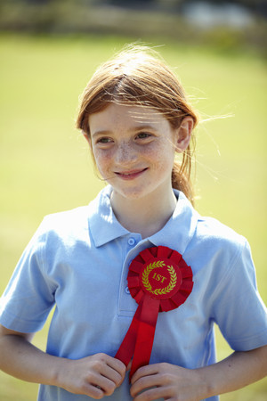 Smiling girl wearing first place ribbon LANG_EVOIMAGES