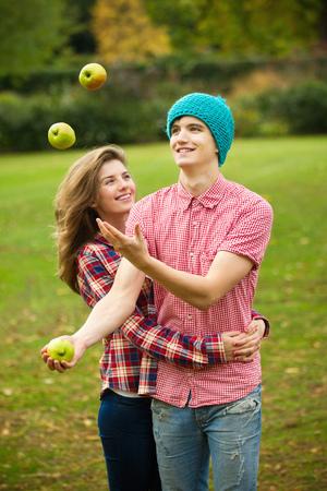 Teenage couple juggling apples in park