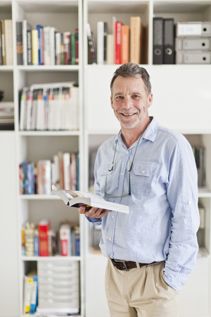 60 64 years: Businessman reading book in office