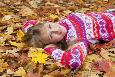 Woman laying in fall leaves LANG_EVOIMAGES