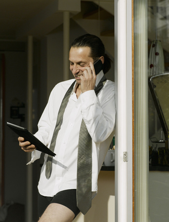 gratified: Businessman dressing on cell phone