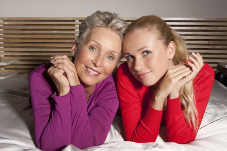 60 64 years: Mother and daughter laying on bed