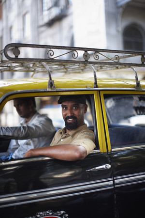 Smiling man riding in taxi cab LANG_EVOIMAGES