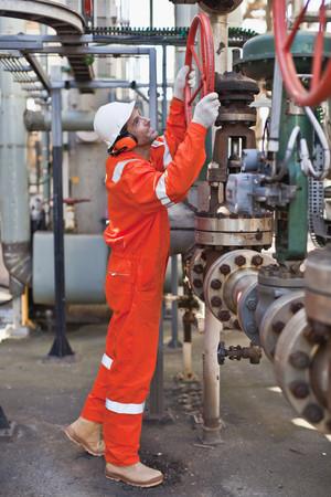 Worker adjusting gauge at oil refinery LANG_EVOIMAGES