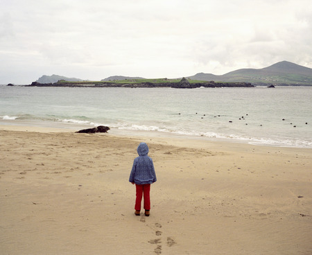 Girl standing on empty beach LANG_EVOIMAGES