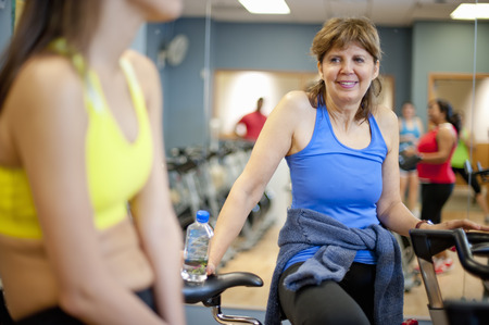 60 64 years: Woman climbing spin machine in gym