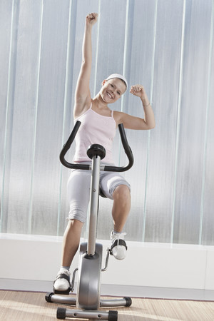 Woman cheering on exercise machine LANG_EVOIMAGES