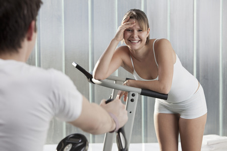 Woman laughing on exercise machine LANG_EVOIMAGES