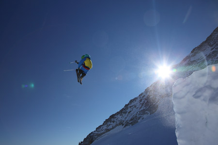 Male skier leaping against clear blue sky LANG_EVOIMAGES