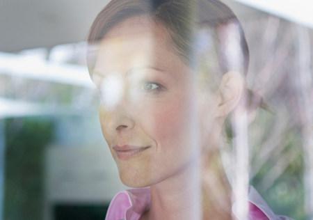 Businesswoman looking through window,portrait LANG_EVOIMAGES