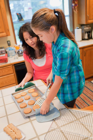50 54 years: Mother and daughter baking cookies