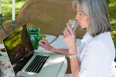 silver surfer: Mature woman using laptop drinking water