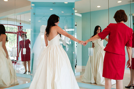 woman mirror: Daughter trying on wedding dress, holding hands