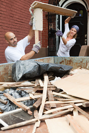 saltar: Couple filling skip with rubble LANG_EVOIMAGES