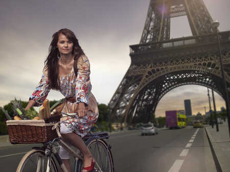 histories: Woman riding bicycle under Eiffel Tower