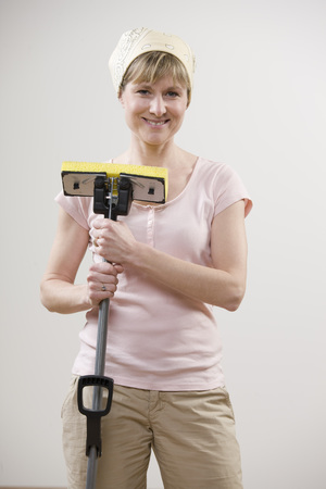 homemakers: Smiling woman holding mop LANG_EVOIMAGES