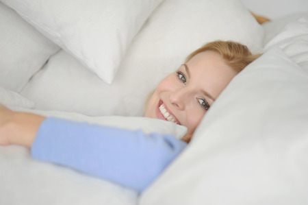 gratified: Smiling woman relaxing in cushions LANG_EVOIMAGES