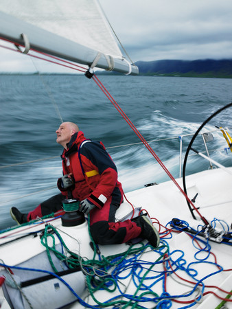remoteness: Man adjusting rigging on sailboat
