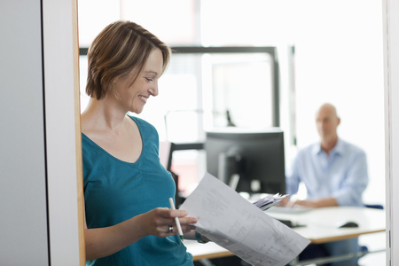 gratified: Businesswoman reading papers in office LANG_EVOIMAGES