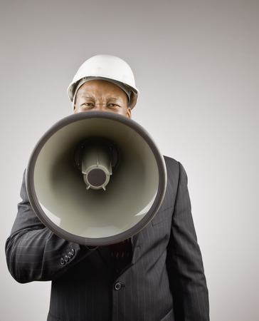 Businessman in hard hat using megaphone