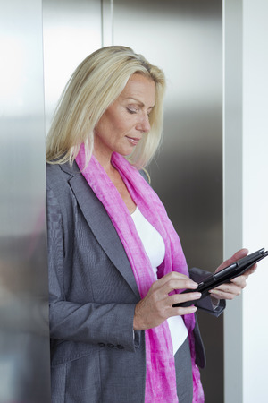 gratified: Businesswoman using tablet in lobby