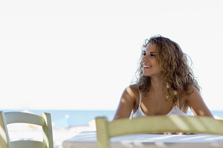 front desk: woman sitting at the table  at the beach