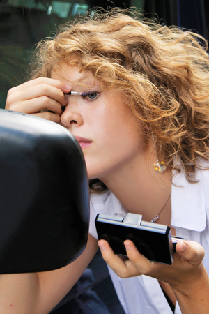 woman mirror: Woman applying makeup in car mirror LANG_EVOIMAGES