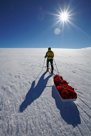 shadowed: Man pulling pack in snow covered field