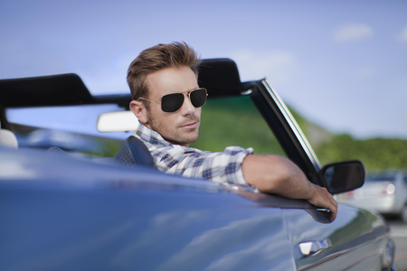 turn away: Man peering out of convertible